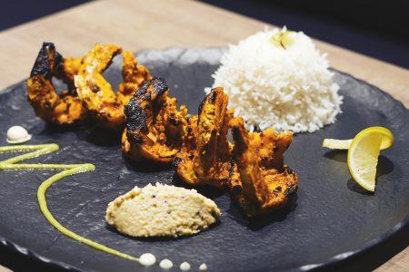 Die delikaten Tandoori Riesengarnelen präsentieren sich farbenfroh auf dem Teller.