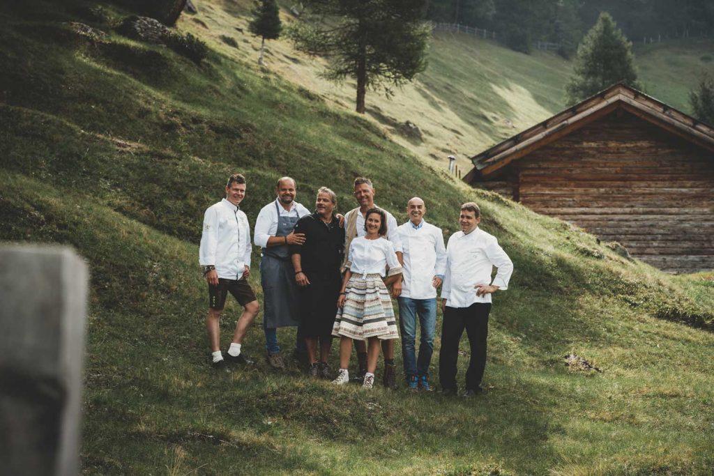 Die fünf Südtiroler Spitzenköche Reimund Brunner, Othmar Raich, Walter Weger, (v. l.) sowie Luis Haller und Gerhard Wieser (v. r.) gemeinsam mit ihren Gastgebern Helli und Nadia Gufler (m.) auf der Gompm Alm in Schenna.